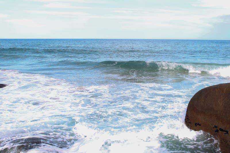 Une mer bleue avec de grandes pierres photo stock