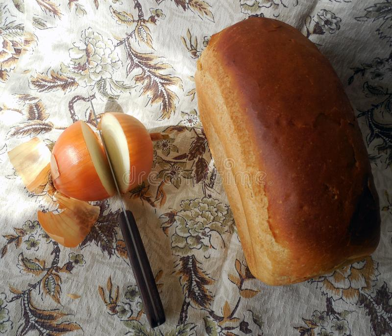 Une miche de pain, des oignons coupés en tranches et un couteau sur une nappe légère de toile photographie stock libre de droits