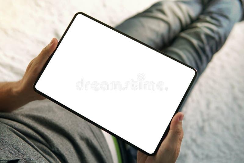 Une moitié inférieure d'un homme s'asseyant sur le lit regardant vers le bas à l'écran vide d'un comprimé à jour Un jeune homme s image stock