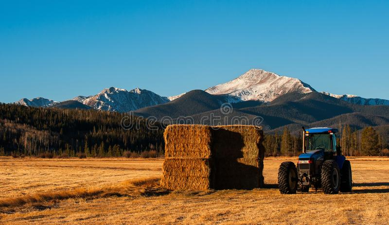 Une montagne se lève au-dessus d'un gisement de tracteur et de foin photos libres de droits