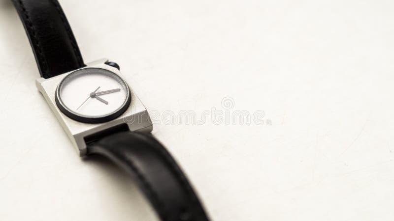 Une montre-bracelet avec les courroies noires sur un fond blanc photographie stock