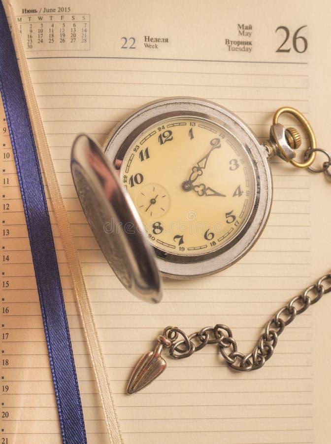 Une montre de vintage avec une chaîne se trouve sur une feuille de carnet photos stock