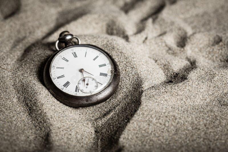 Une montre en gros plan de gousset dans le sable photographie stock