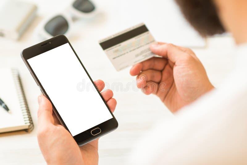 Une moquerie noire de smartphone haute et une carte de crédit dans l'homme d'affaires de mains Carte en ligne de plastique de pai image libre de droits