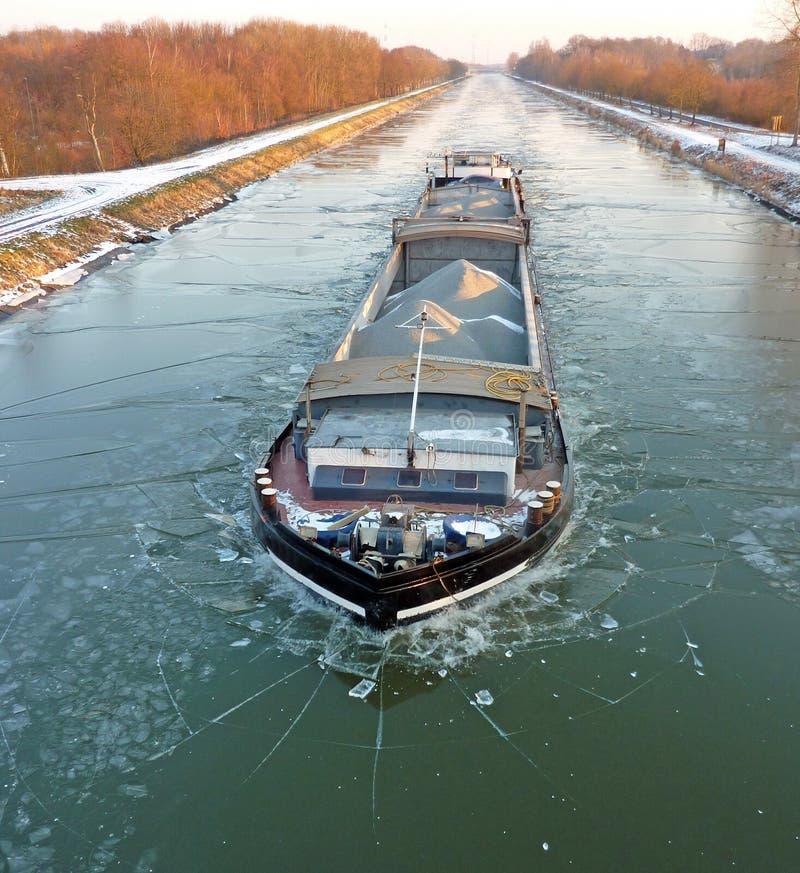 Une navigation de péniche sur la rivière congelée photographie stock libre de droits