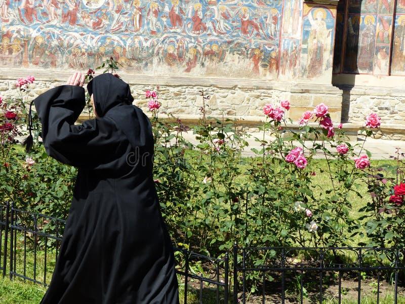 Une nonne vue par derrière avec les mains s'est soulevée dans un monastère du Bucovina en Roumanie photos stock