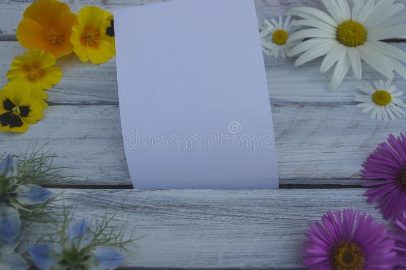 Une note sur une surface en bois encadrée par les fleurs 1 photographie stock