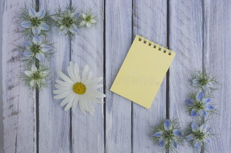 Une note sur une surface en bois encadrée par les fleurs 7 photos stock