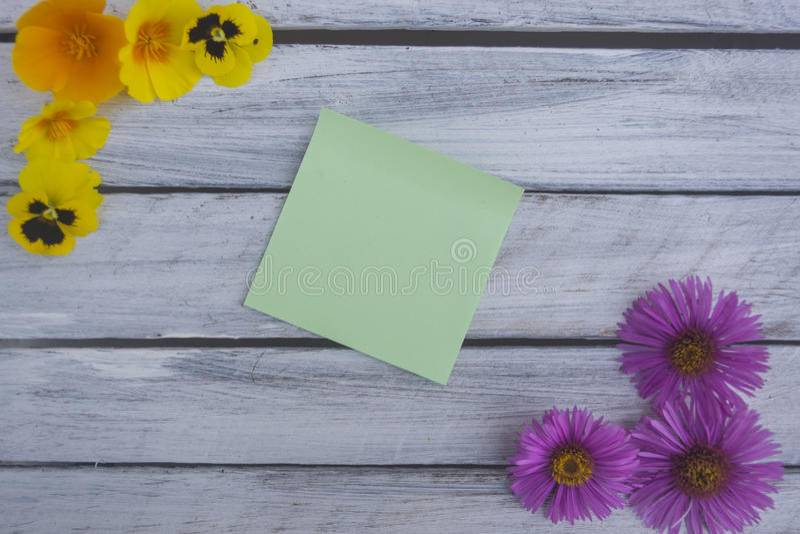 Une note sur une surface en bois encadrée par les fleurs 2 d'été photos stock