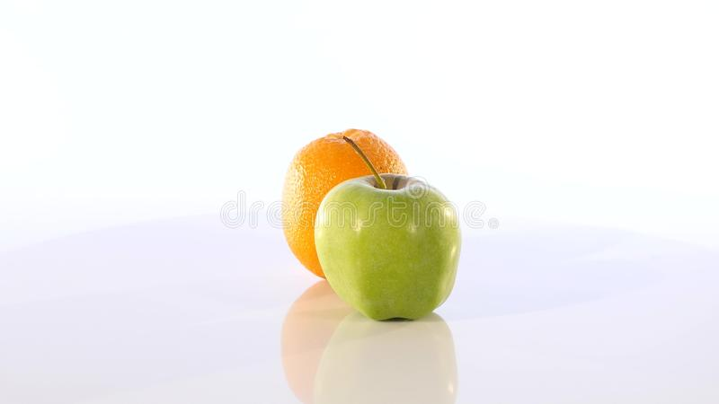 Une orange et une pomme verte Le fruit tourne lentement sur un fond blanc photographie stock libre de droits