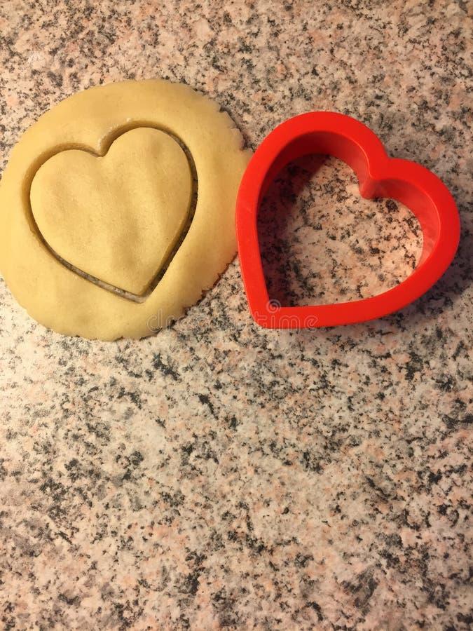 Une pâte de moule et de biscuit de coeur à faire cuire au four pour Noël photographie stock libre de droits