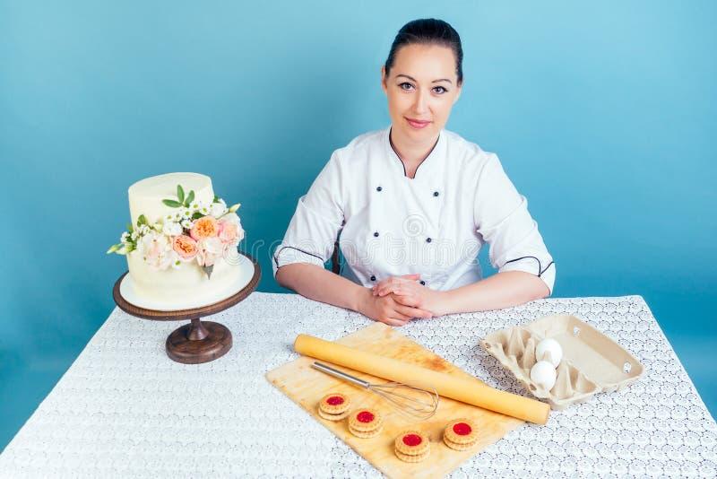 Une pâtissière chef pâtissière décorée d'un gâteau blanc crémeux à deux étages pour l'anniversaire de mariage avec des fleurs fra image libre de droits