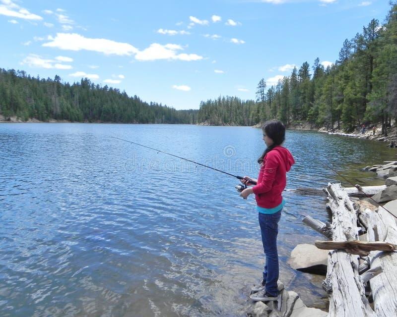 Une pêche de jeune fille dans un lac de montagne image stock