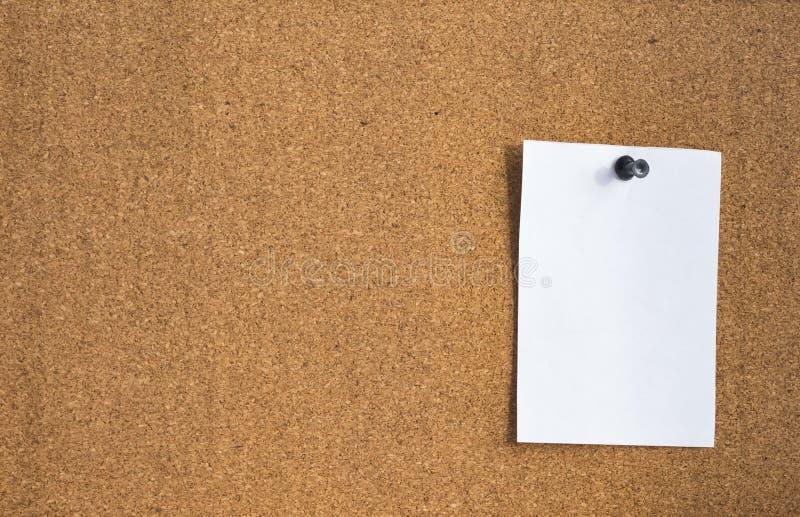 Une page blanche de papier jointe à un panneau de liège photos stock