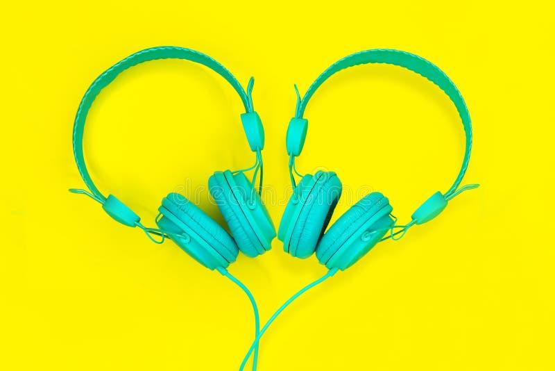 Une paire d'écouteurs de turquoise sous forme de coeur sur un fond jaune Festival de musique d'amour d'été photographie stock libre de droits