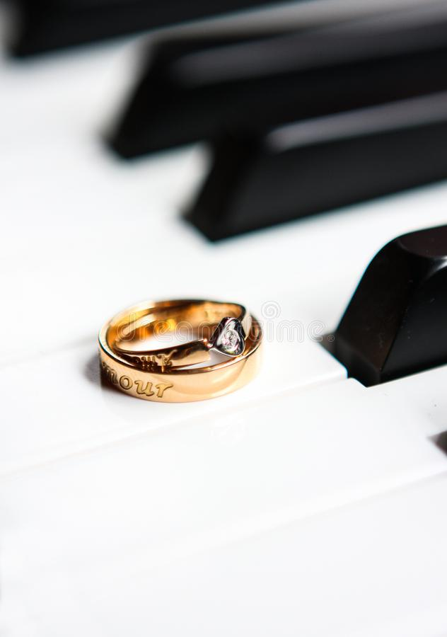 Une paire d'anneaux de mariage sur le piano photographie stock libre de droits