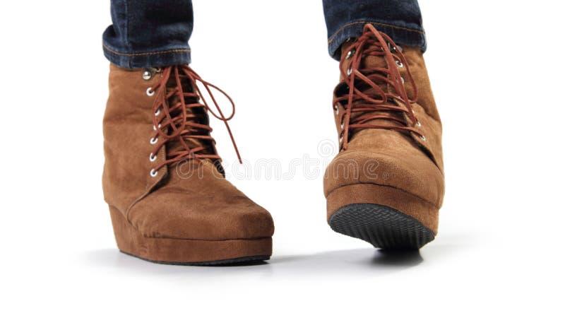 Une paire de bottes brunes de femmes dans le geste espiègle photos stock