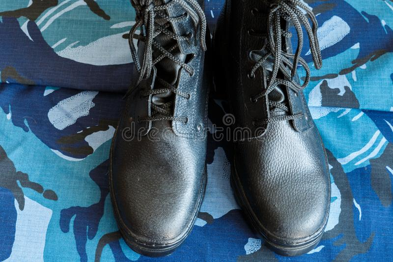 Une paire de bottes noires d'armée sur le tissu avec le camouflage bleu Aucune personnes Bottes d'armée pour le soldat La partie  photographie stock libre de droits