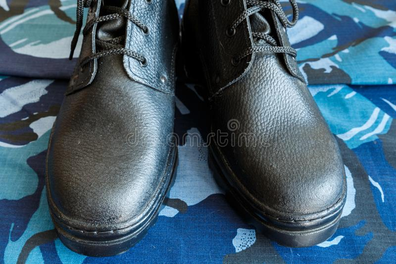 Une paire de bottes noires d'armée sur le tissu avec le camouflage bleu Aucune personnes Bottes d'armée pour le soldat La partie  photos stock
