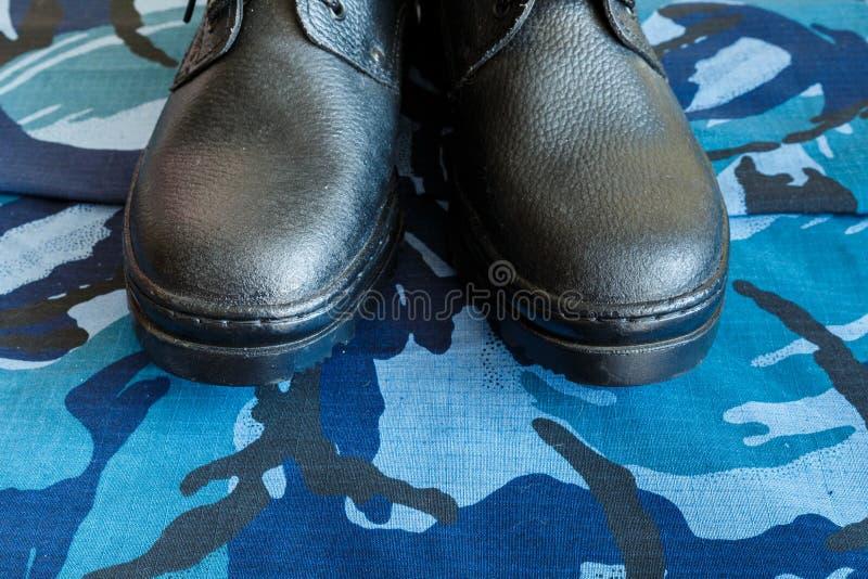 Une paire de bottes noires d'armée sur le tissu avec le camouflage bleu Aucune personnes Bottes d'armée pour le soldat La partie  photos libres de droits