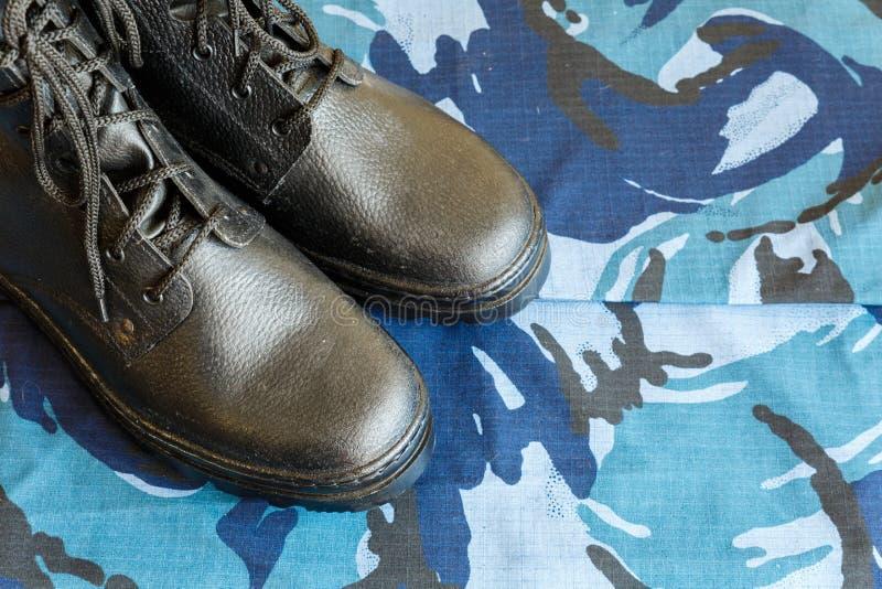 Une paire de bottes noires d'armée sur le tissu avec le camouflage bleu avec le copispace pour le texte images stock
