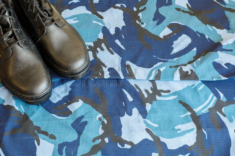 Une paire de bottes noires d'armée sur le tissu avec le camouflage bleu avec le copispace pour le texte photos libres de droits