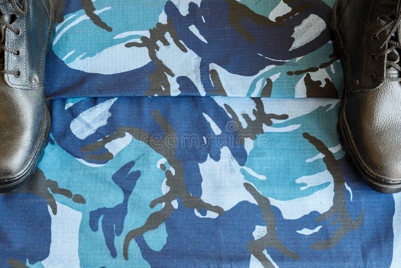 Une paire de bottes noires d'armée sur le tissu avec le camouflage bleu avec le copispace pour le texte photo stock