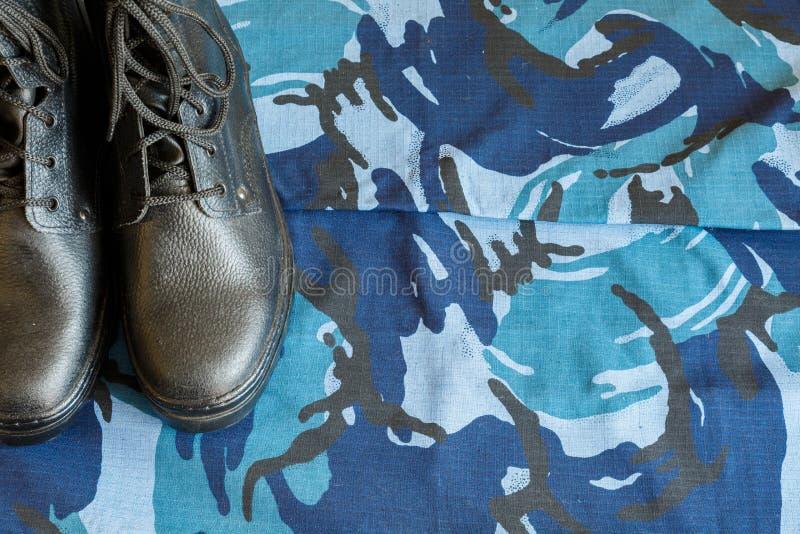 Une paire de bottes noires d'armée sur le tissu avec le camouflage bleu avec le copispace pour le texte photographie stock