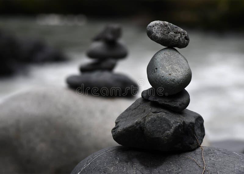 Une paire de cairns par la rivière photographie stock libre de droits