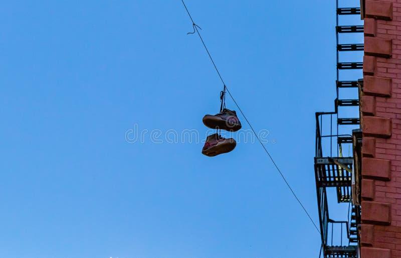Une paire de chaussures accrochées sur un fil sur une rue à New York City image libre de droits