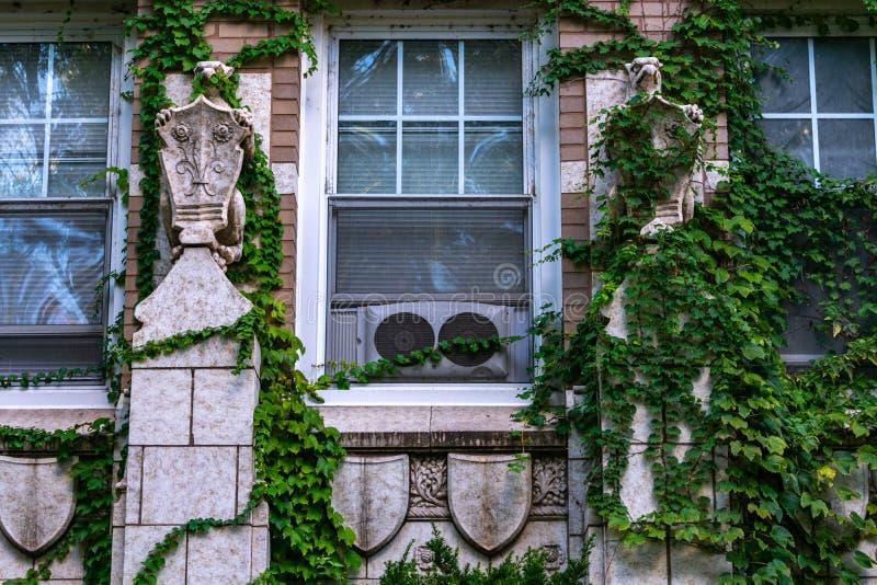 Une paire de gargouilles du côté d'un vieil immeuble urbain photographie stock