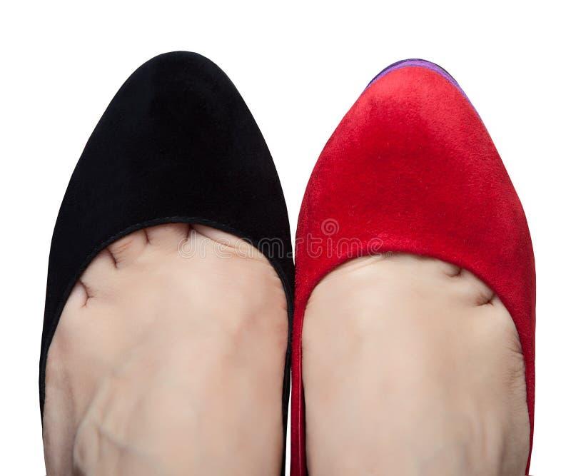 Une paire de jambes femelles dans des chaussures avec différentes couleurs image stock
