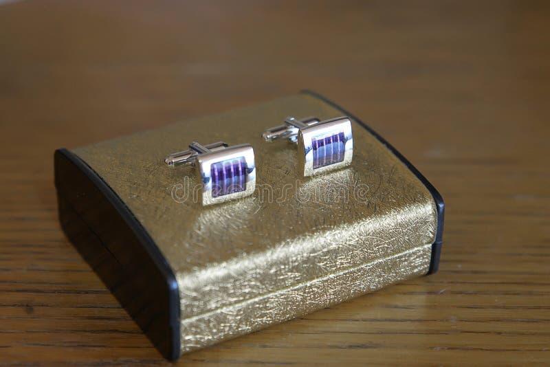 Une paire de liens de manchette d'argent, de platine ou d'or blanc avec l'émail bleu placé sur une boîte d'or élégante photos libres de droits