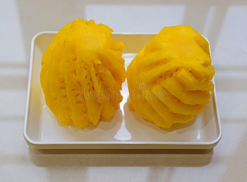 Une paire de maison a coupé et a épluché des ananas d'un plat rectagular blanc photos libres de droits