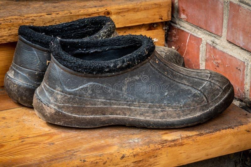 Une paire de vieilles couvre-chaussures noires sales de bottes en caoutchouc au seuil de la maison Fin vers le haut image stock