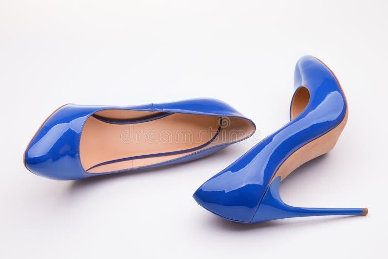 Une paire de women& x27 ; chaussures de cuir verni bleues de s sur un fond blanc photo libre de droits