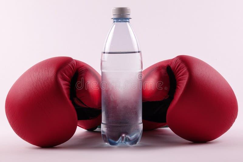 Une paire des gants de boxe et d'une bouteille de l'eau photographie stock