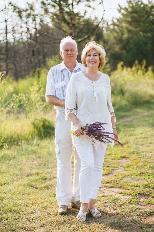 Une paire des personnes âgées dans des vêtements de toile blancs étreint en nature et sourit, dans les mains un bouquet des fleur photos libres de droits
