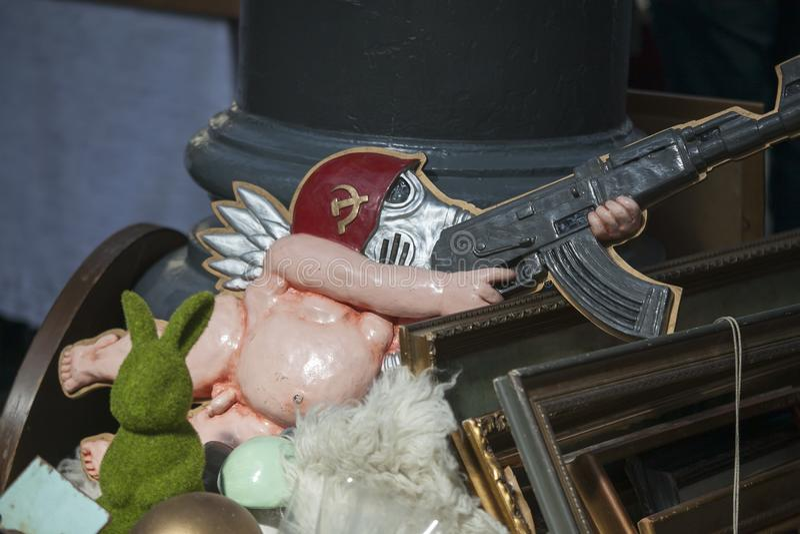 Une parodie de l'Union Soviétique L'ange nu en plastique dans un masque de gaz et le casque d'un soldat soviétique avec une kalac photographie stock