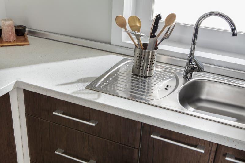Une partie d'évier de cuisine moderne avec des tiroirs et des poignées photographie stock