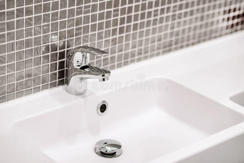 Une partie d'intérieur de salle de bains, d'évier et de robinet de chrome photographie stock libre de droits