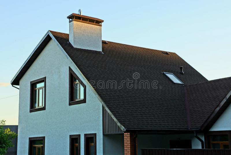 Une partie d'une maison privée avec des fenêtres et un toit sous une tuile brune contre photographie stock libre de droits