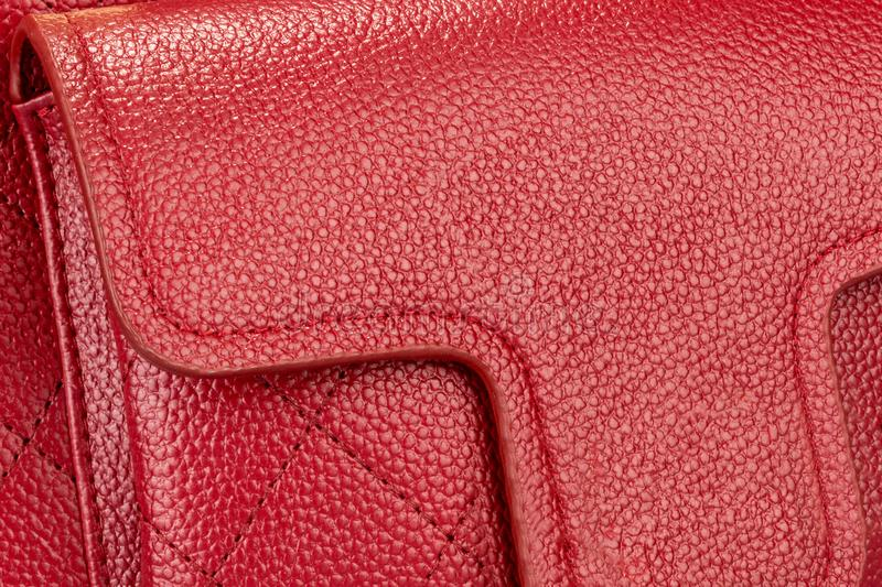 Une partie d'un sac femelle en cuir rouge avec une poche et une texture images libres de droits