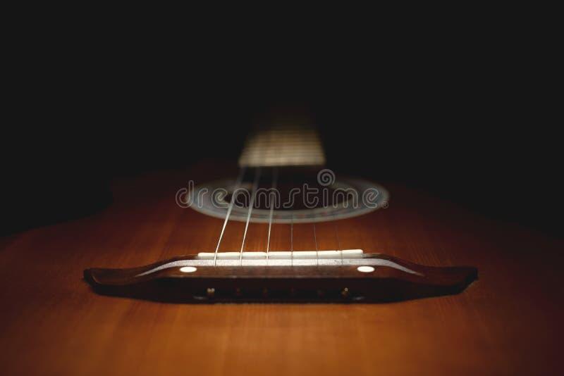 Une partie d'une vieille guitare brune avec des ficelles sur un fond en bois foncé photo stock