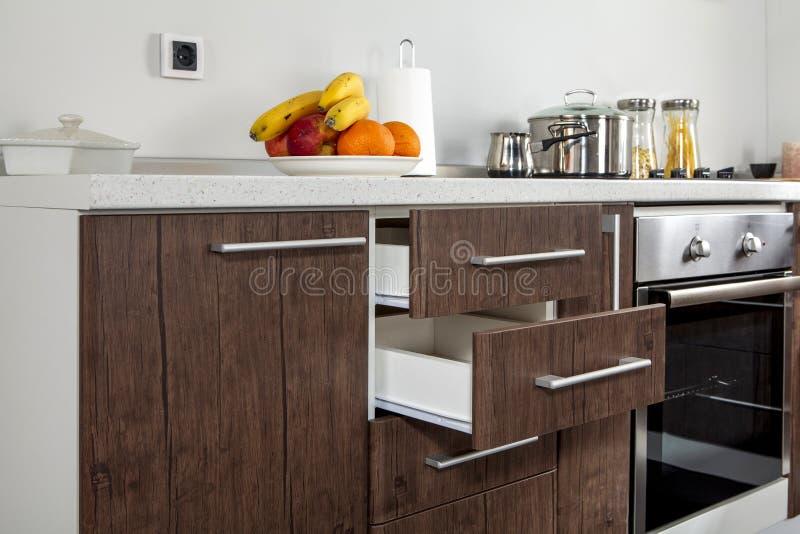 Une partie de cuisine moderne avec le four électrique de fourneau, tiroirs, poignée photographie stock