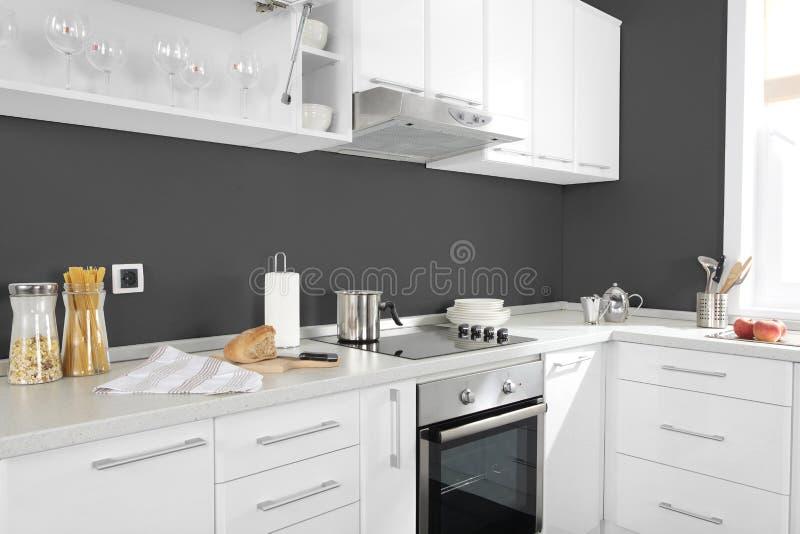 Une partie de cuisine moderne avec les petits groupes et les tireurs électriques de four de fourneau image stock