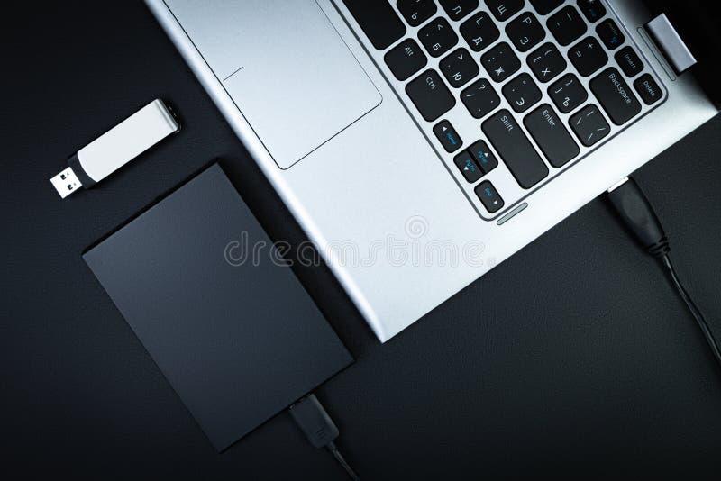 Une partie de l'ordinateur portable avec une unité de disque dur externe et une commande instantanée images stock