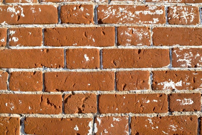 Une partie de la fin de mur d'une vieille maison en dehors de brique rouge avec le blanc éclabousse le mastic enlevé pour la rest photos stock