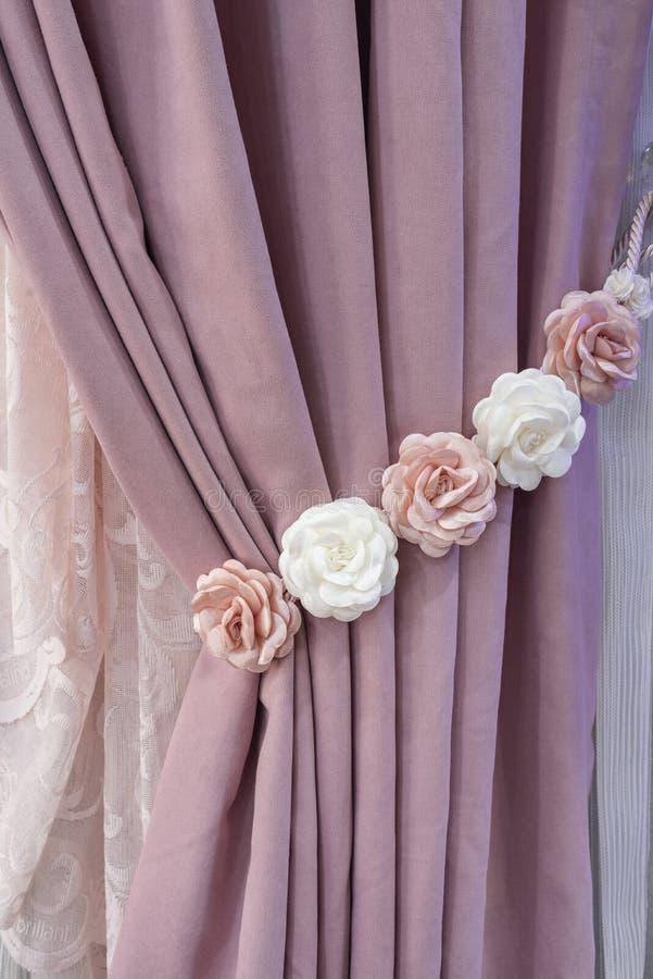 Une partie de rideau admirablement drapé sur la fenêtre dans la chambre Embrasse rose florale Fermez-vous du rideau empilé Rideau images libres de droits