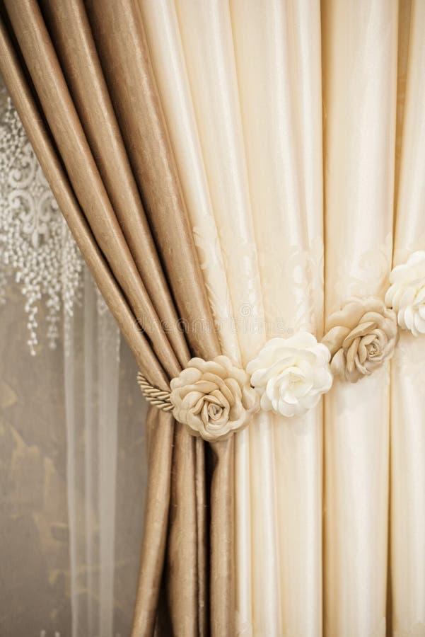 Une partie de rideau admirablement drapé sur la fenêtre dans la chambre Embrasse florale Fermez-vous du rideau empilé Cu de luxe  image stock